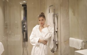 woman-in-white-robe-standing-in-front-of-glass-door-3940696